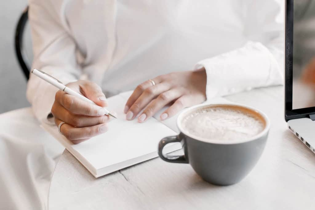 Woman writing in her journal enjoying coffee: best fall flavored coffee to try