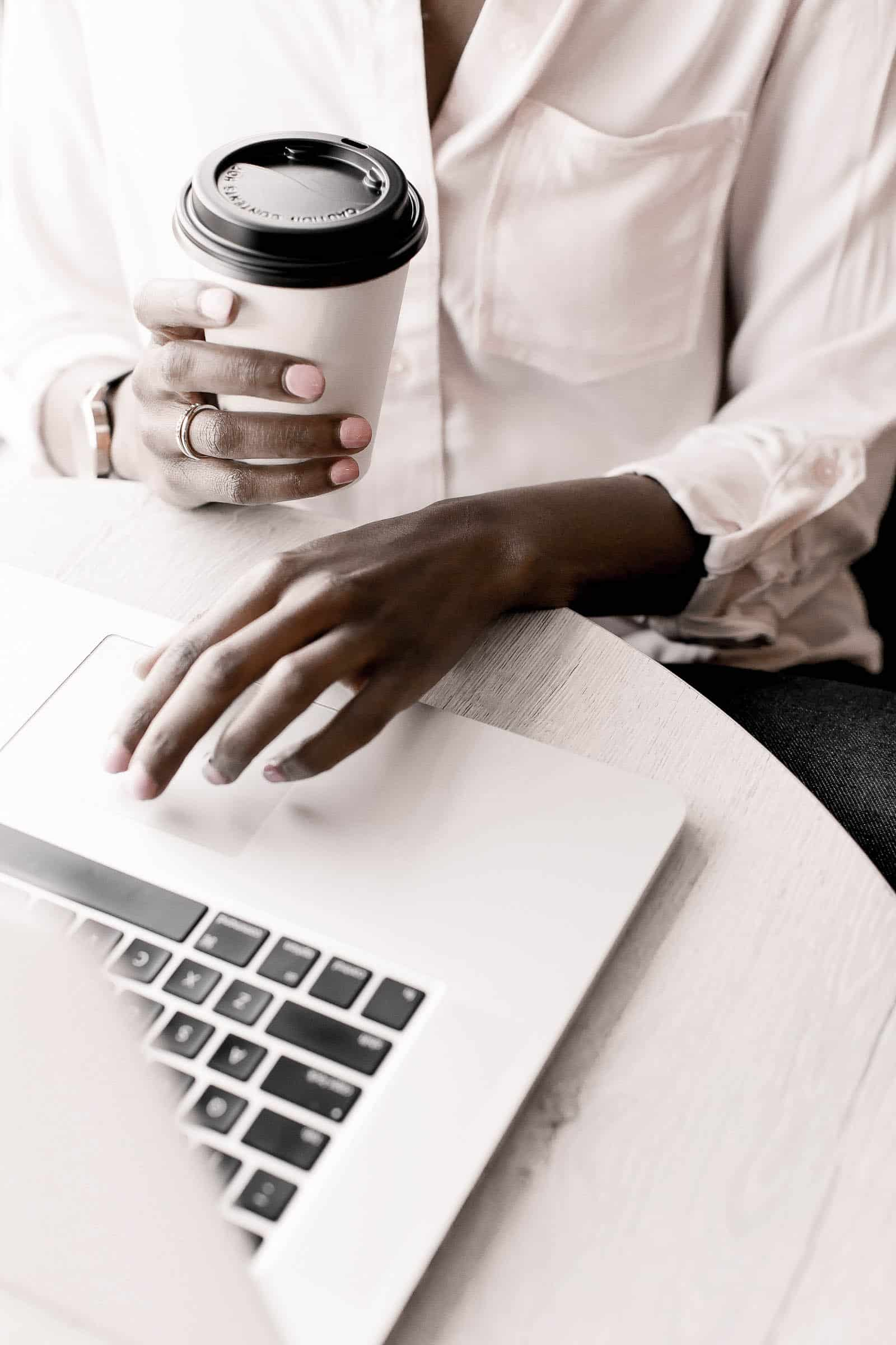 Woman with a coffee in her hand using a silver laptop on a white surface