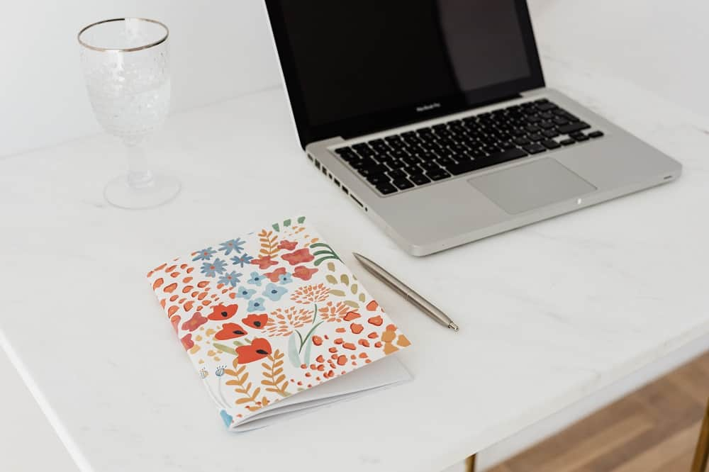 Floral planner on a surface along with a macbook and a gold pen