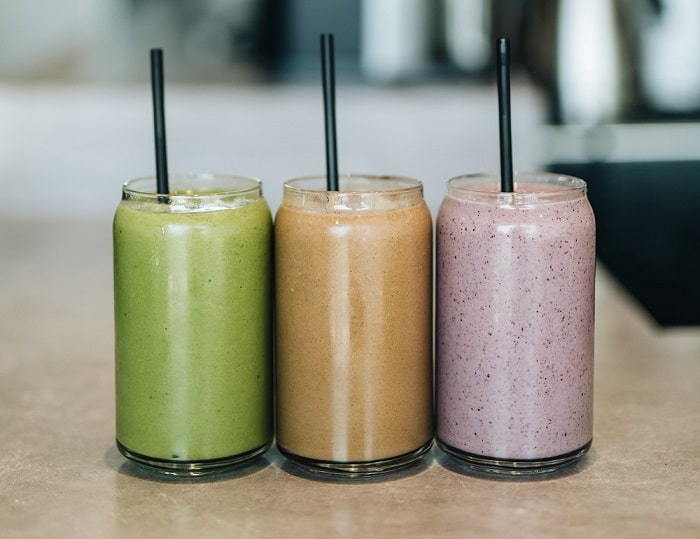 Three bright smoothies in clear glasses lined up on a tabletop