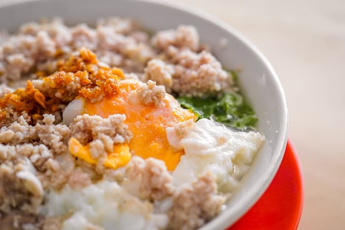 Japanese breakfast bowl with rice, egg, nori, and crumbled chicken